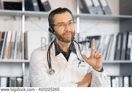 Doctor With Headset Gives Advice Online. He Listens Attentively And Draws Attention To The Patient W
