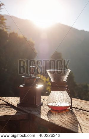 Hot Arabica Coffee And Vintage Coffee Drip Equipment On Wooden Table In The Morning With Mountain An