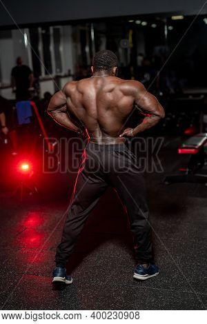 Strong Back Of Muscular Bodybuilder Poses To The Camera In Modern Gym With Dark Light. Bodybuilding,