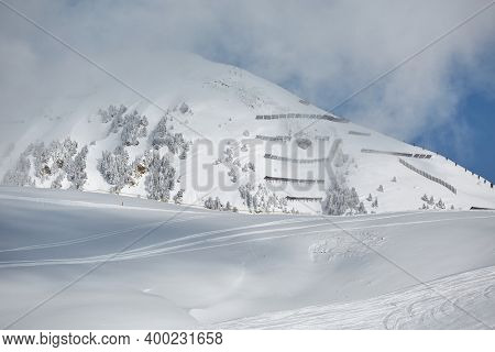 Snowy mountain slope with avalanche barriers installed on the hillside