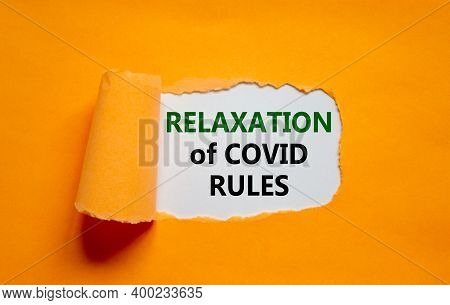 Relaxation Of Covid Rules Symbol. Words 'relaxation Of Covid Rules' Appearing Behind Torn Orange Pap