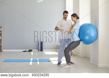 Professional Osteopath Controlling Womans Position During Exercising With Fitness Ball