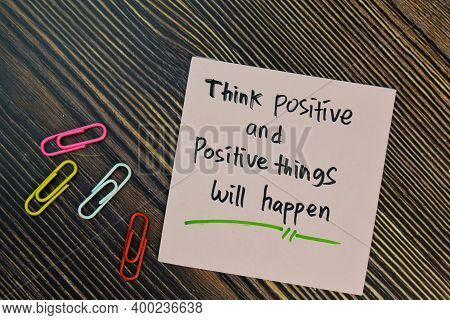 Think Positive And Positive Things Will Happen Write On Sticky Notes Isolated On Wooden Table. Motiv