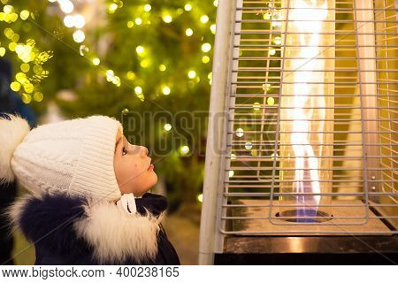 A Little Girl In A Warm Hat Looks At The Flame Of A Gas Burner Warming At A Christmas Market In The