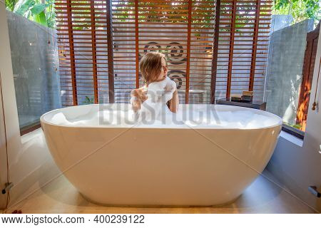 Smiling Sensual Woman Relaxing, Take A Bath In Bathtub With Soap Foam With Flowing Water In Sun Rays