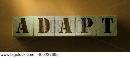 Wooden Blocks With The Text: Adapt. Adaptation To Changing Reality While Coronavirus Quarantine Conc