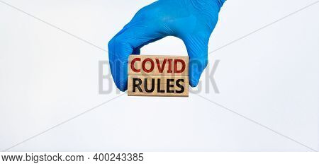 Medical And Covid-19 Pandemic Coronavirus Symbol. Hand In Blue Glove Holds Wooden Blocks With Words