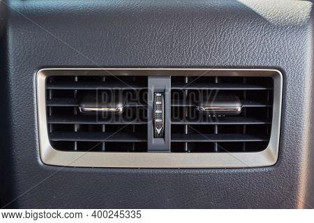 Car air vents providing airflow for backseat passengers