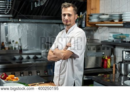 Young successful chef of modern restaurant in white uniform crossing arms by chest while standing by table in the kitchen before cooking salad