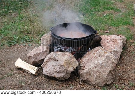 Tourist Bowler With Food On Bonfire, Cooking In The Hike, Outdoor Activities. Preparation Of Pilaf.