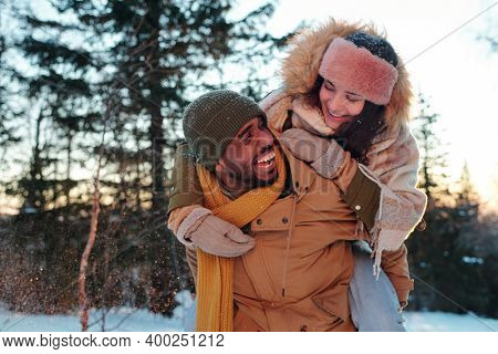 Laughing African guy in winterwear giving his happy girlfriend piggyback while having fun and enjoying winter weekend in natural environment