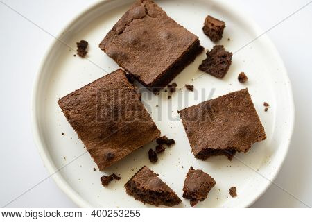 Close Up Of Brownie Pie Bars With Chocolate On A White Plate. Top View Of Mouthwatering Tortillas Wi
