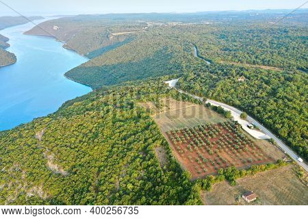 A Winding Water Channel In A Mountainous Area. A Road Winds Through The Mountain Watershed. There Is