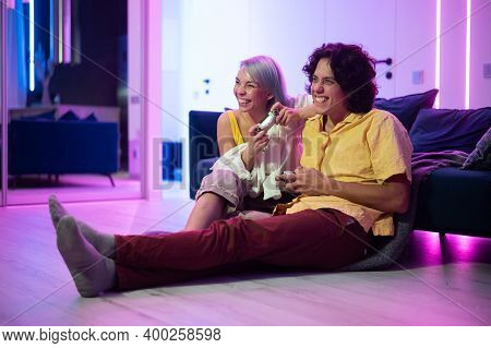 Happy Young People Playing Video Games On Console While Sitting On Couch In Front Of Tv. Millennial