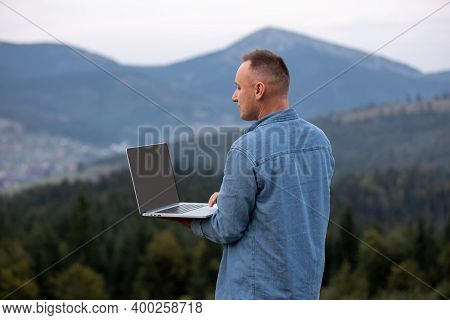 Man Working Outdoors With Laptop In Mountains. Concept Of Remote Work Or Freelancer Lifestyle. Cellu