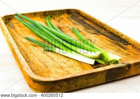 Green Spring Onion Scallion Feathers On Wooden Tray On White Table Background. Close Up. Selective F