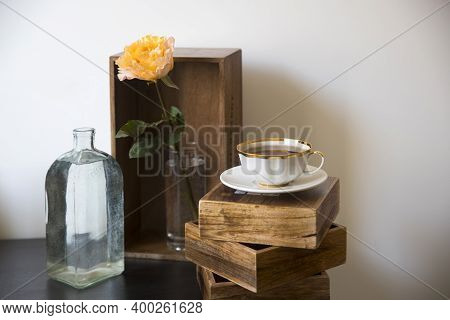 Orange Rose Candlelight In Glass Vase. Tea In A Porcelain Cup With A Gold Border On Three Wooden Box