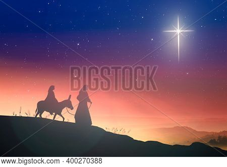 Christmas Religious Nativity Concept: Silhouette Pregnant Mary And Joseph With A Donkey On Star Of C