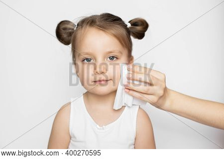 Kids Hygiene And Skincare Concept, Wet Wipe Promo. Close Up Of Mother Hand Wiping The Baby Face Skin