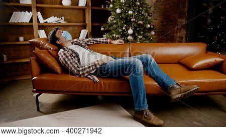 Young Man In Mask Lies On Sofa And Stares At Ceiling, Suffering From Loneliness And Home Isolation D