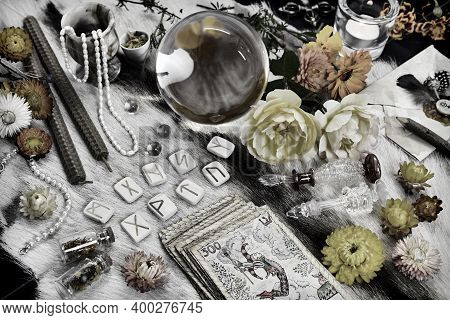 Styled Still Life With Tarot Cards Deck, Magic Crystal, Runes, Candles And Flowers On Witch Table. E