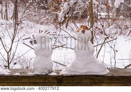 Two Miniature Snowmen, Depicting A Boy And Girl On A Wooden Railing In Frick Park On A Winter Day In