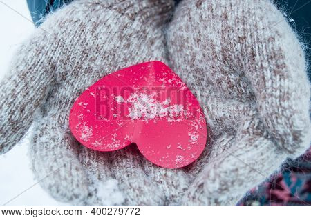 Womens Hands In Knitted Warm Wool Gloves Hold A Red Heart, Against The Background Of Snow, In Winter