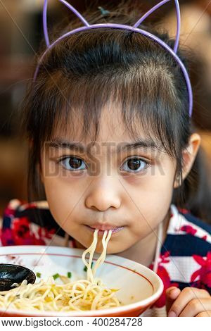 Female Asian Child While Eating Noodles. Child Eating Ramen Noodles Smiling And Enjoying The Food. C
