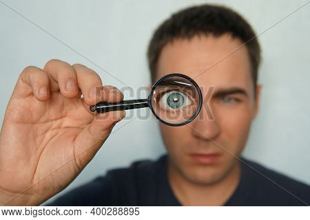 Potrait Of A Man Holding Magnifying Glass And Looking Through It Srewing Up One Eye. Funny View To M