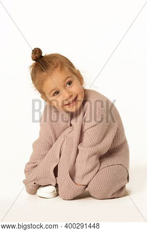 Cute Little Blond Baby Girl Sit The Floor In Pink Knitted Pant Suit Full Body Photo