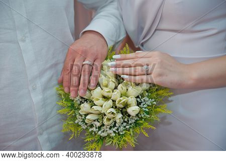 They Put Their Hands On The White Rose . Bride And Groom With Engagement Gold Rings Put Their Hands
