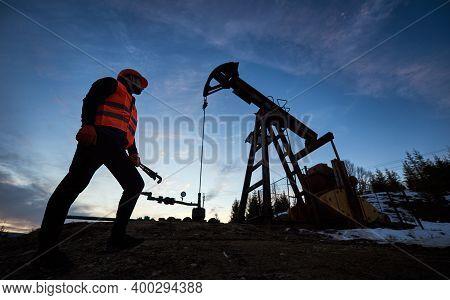 Low Angle Of Male Oil Worker Standing Near Petroleum Pump Jack Under Beautiful Evening Sky. Petroleu