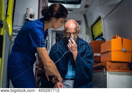 Injured Man Sitting With An Oxygen Mask In An Ambulance Car, A Young Nurse Is Holding His Hand.
