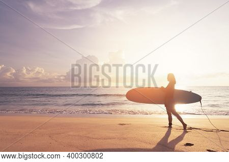 Woman Hold Surfboard Standing At Tropical Sunset Beach Background. Summer Vacation And Sport Adventr