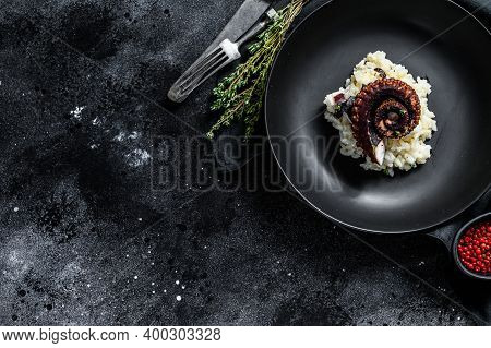 A Portion Of Risotto With Octopus Tentacles. Black Background. Top View. Copy Space