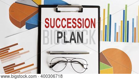 White Sheet With The Text Of Succession Plan On The Background Of Documents And Graphs.