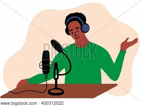 African Black Man In Green Clothes Is Doing Live Podcast. Male Podcaster Talking To Microphone Recor