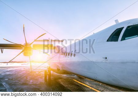 A Close-up Of The Fuselage Of A White Passenger Turboprop Aircraft On The Winter Airport Apron In Th
