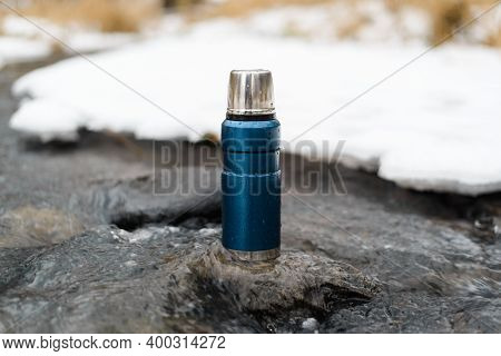 Blue Vacuum Thermos Close-up Outside In Winter. Camping Thermos Standing On A Stone In A Winter Stre