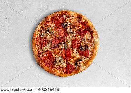 Tasty Pizza With Salame And Mushrooms On Bright Concrete Surface. Top View Of Sliced Pizza.