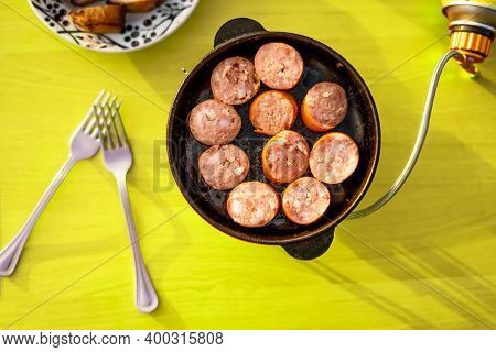Sausage Fried In A Frying Pan Top View, Cooking In Nature. Heating With A Gas Burner.