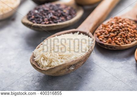 Organic White Jasmine Rice, Unpolished Black And Brown Rice, Riceberry  In Wooden Spoons. Assortment