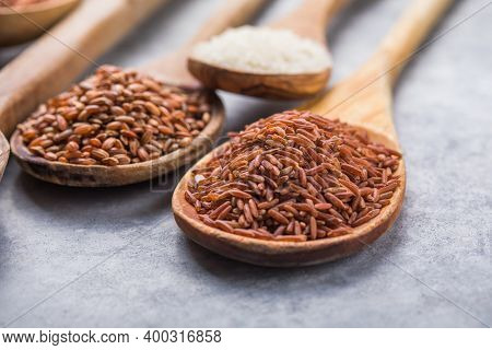 Organic White Jasmine Rice, Unpolished Black And Brown Rice, Riceberry  In Wooden Spoons. Unpolished