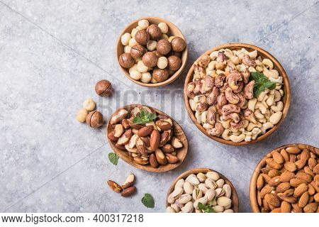 Assortment Of Nuts In A Wooden Bowls, On A Gray Background. Hazelnuts, Pistachios, Almonds, Brazil N