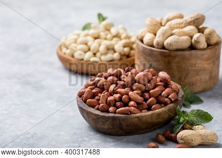 Raw Dried Fresh Peanut Nuts On A Stone Background. Peanut In Nutshell On Rustic Table In Bowl Or Bur