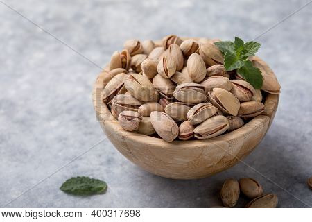 Pistachio Nuts In A Brown Bowl On A Concrete Background. Healthy Eating Concept. Pistachios Scattere