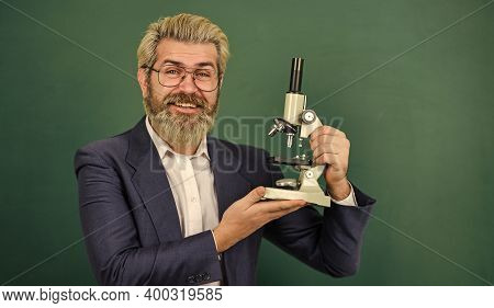 Fascinating Research. Teacher With Microscope. Man Hipster Classroom Chalkboard Background. Biologic