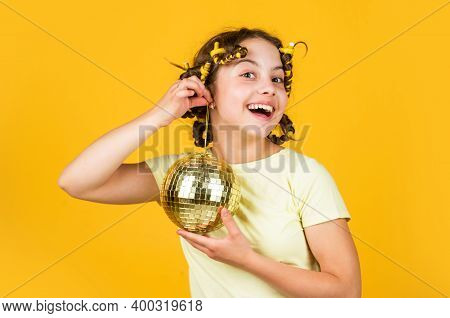 Disco Ball Decoration. Lovely Girl With Disco Ball. Fashion Girl Posing In Curlers On Yellow Wall. S