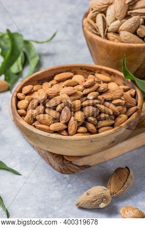 Unshelled Almonds In Bowl With Leaf. Almond Nuts In Wooden Shovel, Almonds With Shell In Bamboo Bowl