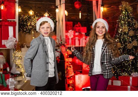 Boy And Girl Santa Claus Hats. Kids Lovely Friends Meet Christmas Holiday. Joy And Noel. Family Cele